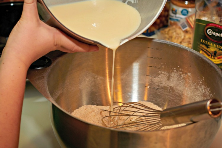 Pour the wet ingredients into the dry to create the banana Nutella pancakes batter.