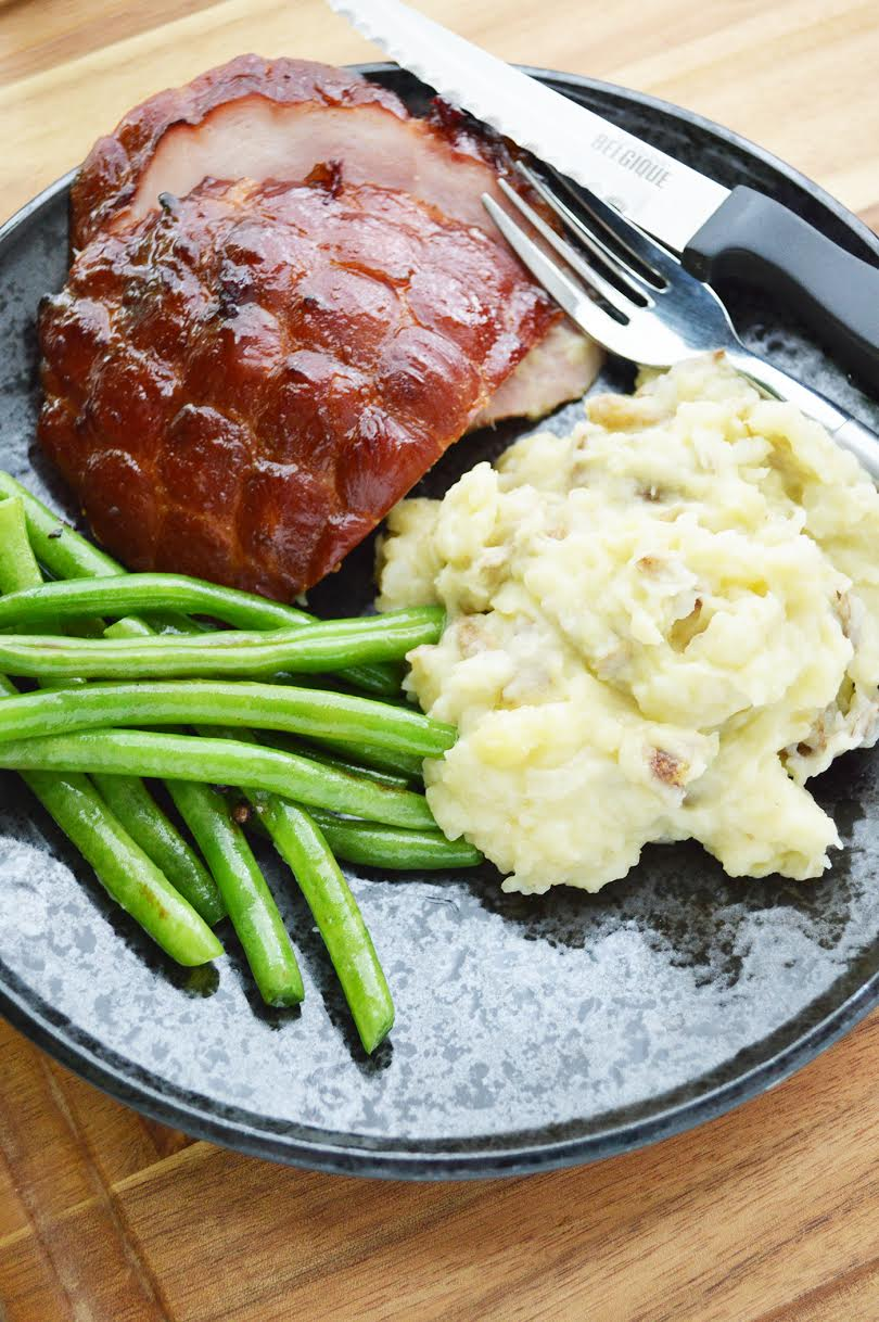 Brown sugar glazed ham recipe with mashed potatoes and green beans on a plate.
