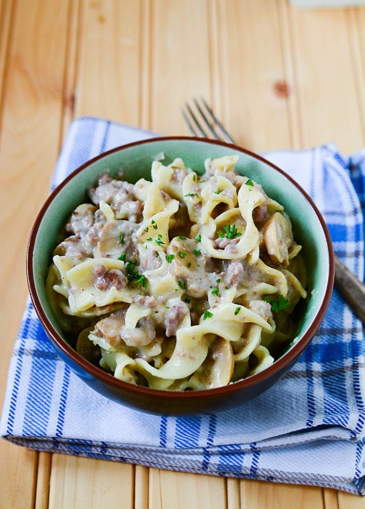 Bowl of slow cooker ground beef stroganoff on a pine table.