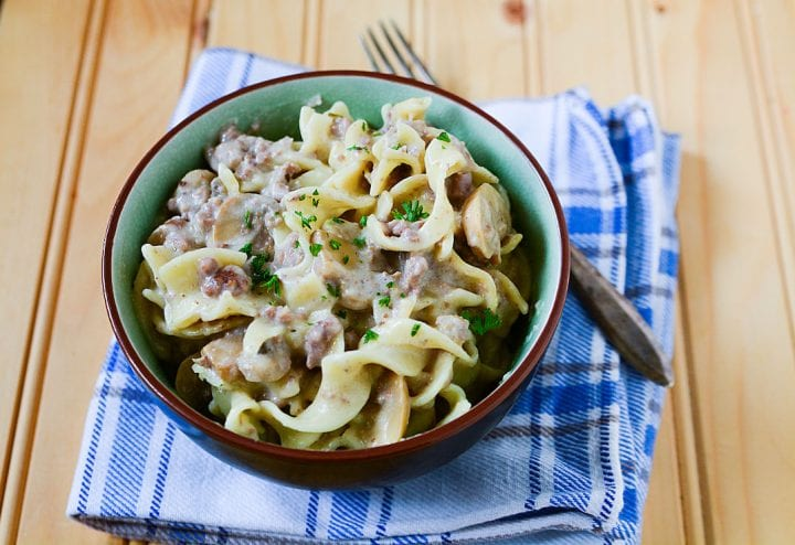 Slow cooker ground beef stroganoff in green and brown bowl on a blue checked tablecloth.