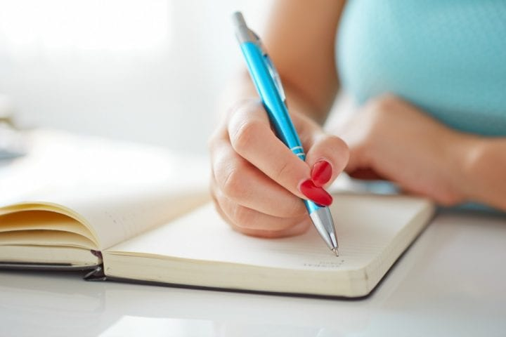 Close up of a woman's hand while she is journaling.
