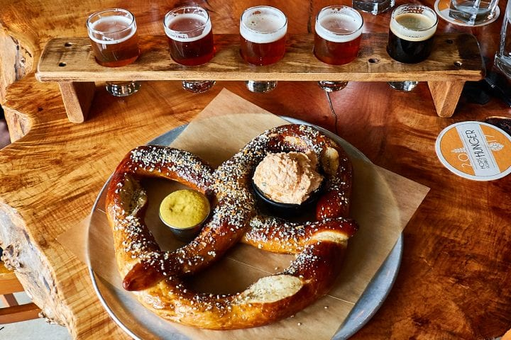 Large pretzel served with beer tasting shots.