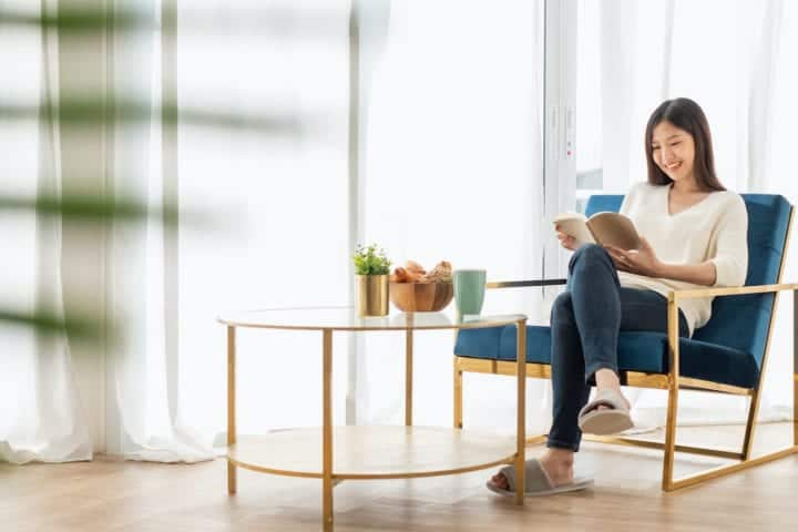 woman smiling reading a book minimalist furniture